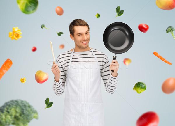 Feliz homem cozinhar avental panela colher Foto stock © dolgachov