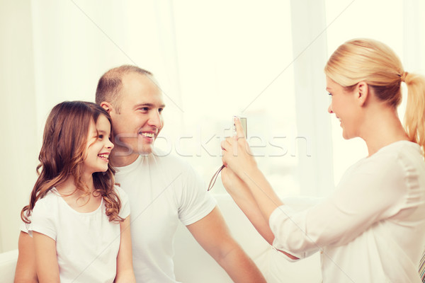 happy mother taking picture of father and daughter Stock photo © dolgachov