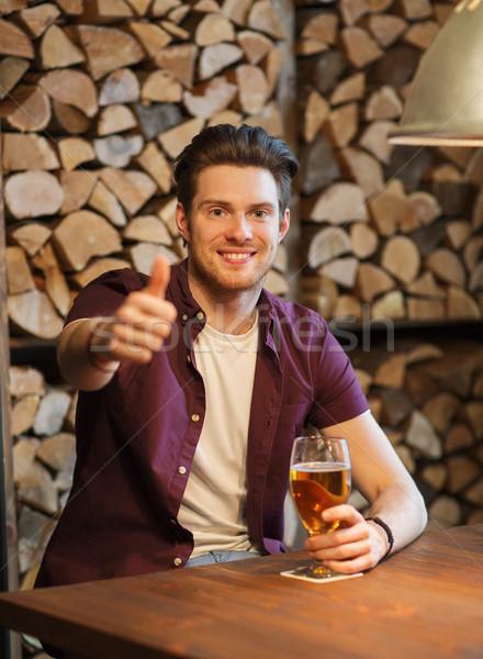 happy man with beer showing thumbs up at bar Stock photo © dolgachov