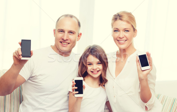 parents and little girl with smartphones at home Stock photo © dolgachov