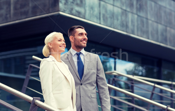 smiling businessmen standing over office building Stock photo © dolgachov