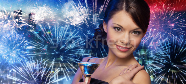 smiling woman with cocktail over firework in city Stock photo © dolgachov