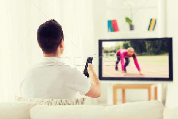 man watching sport channel on tv at home Stock photo © dolgachov