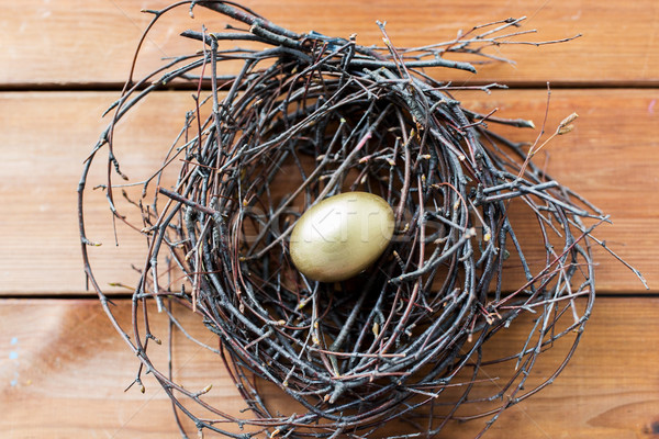 close up of golden easter egg in nest on wood Stock photo © dolgachov