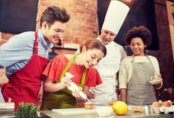 happy friends and chef cook baking in kitchen Stock photo © dolgachov