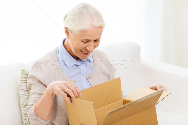 happy senior woman with parcel box at home Stock photo © dolgachov
