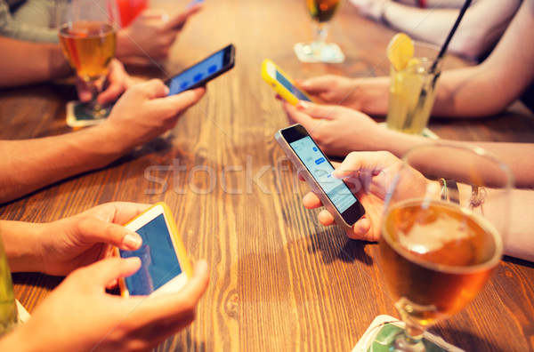 close up of hands with smartphones at restaurant Stock photo © dolgachov
