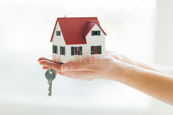 close up of hands holding house model and keys Stock photo © dolgachov