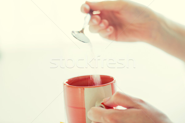 close up of woman hands adding sugar to tea cup Stock photo © dolgachov