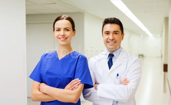 Uśmiechnięty lekarza biały płaszcz pielęgniarki szpitala Zdjęcia stock © dolgachov