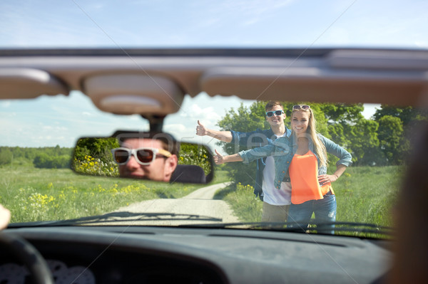 couple hitchhiking and stopping car on countryside Stock photo © dolgachov