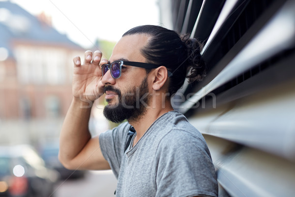 happy man with beard and sunglasses on city street Stock photo © dolgachov