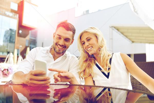 happy couple with smatphone at restaurant terrace Stock photo © dolgachov