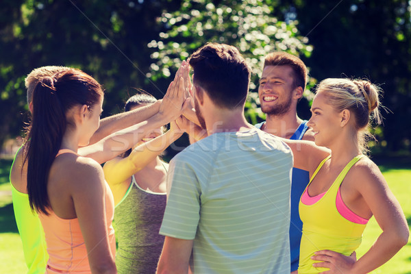 group of happy friends making high five outdoors Stock photo © dolgachov