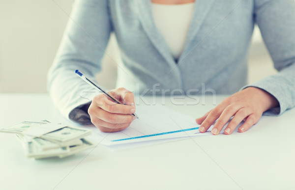 close up of hands with money filling tax form Stock photo © dolgachov
