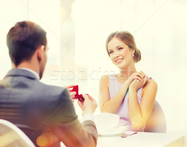 excited young woman looking at boyfriend with ring Stock photo © dolgachov