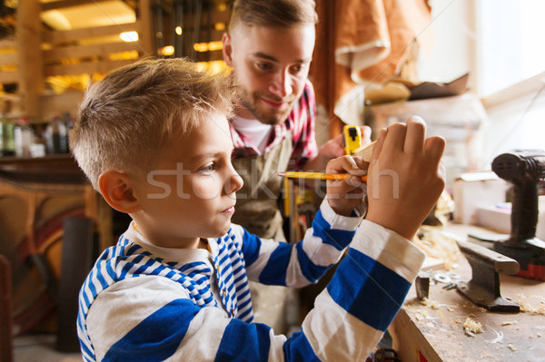 father and son with ruler measure wood at workshop Stock photo © dolgachov