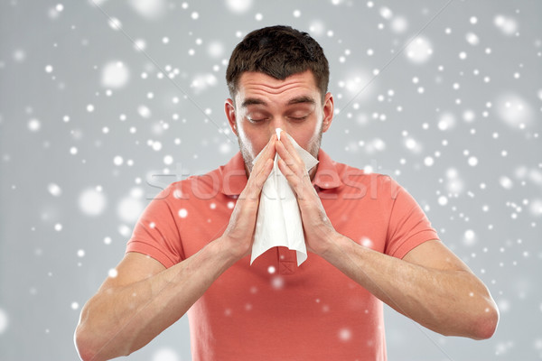sick man with paper wipe blowing nose over snow Stock photo © dolgachov