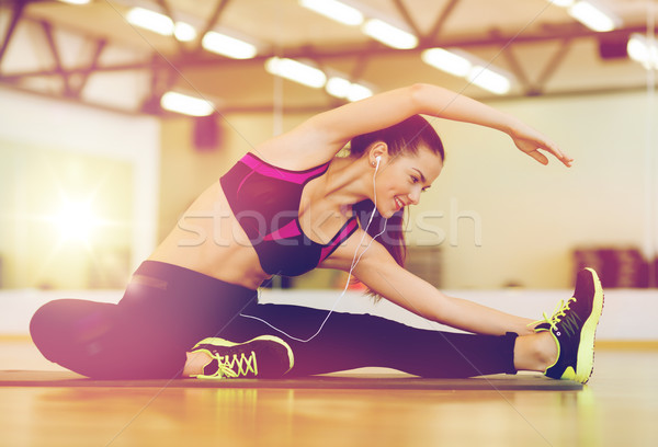 Stock photo: stretching young woman with earphones in the gym
