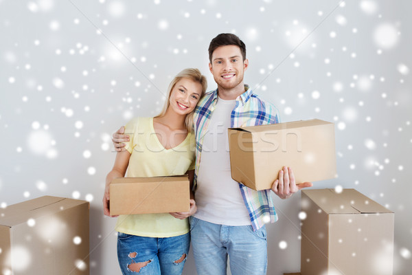 smiling couple with boxes moving to new home Stock photo © dolgachov