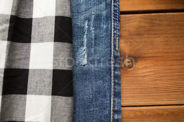 close up of checkered shirt and jeans on wood Stock photo © dolgachov