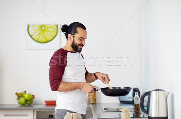 man with frying pan cooking food at home kitchen Stock photo © dolgachov
