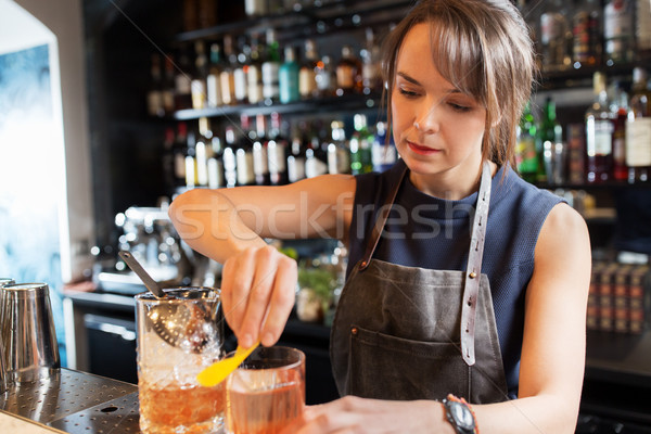 barmaid with glass and jug preparing cocktail Stock photo © dolgachov