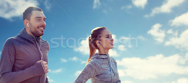 happy couple with earphones running over blue sky Stock photo © dolgachov