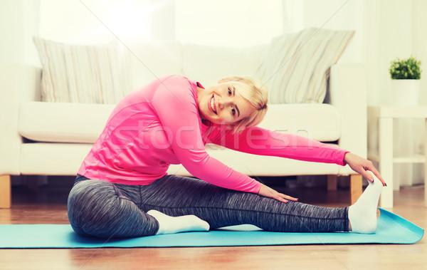 happy woman stretching leg on mat at home Stock photo © dolgachov