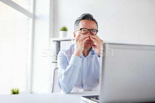 Stock photo: tired businessman in glasses with laptop at office