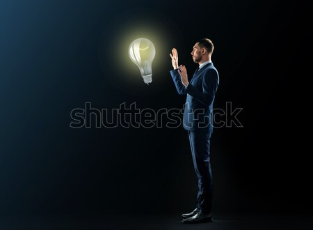 businessman with lightbulb over black background Stock photo © dolgachov