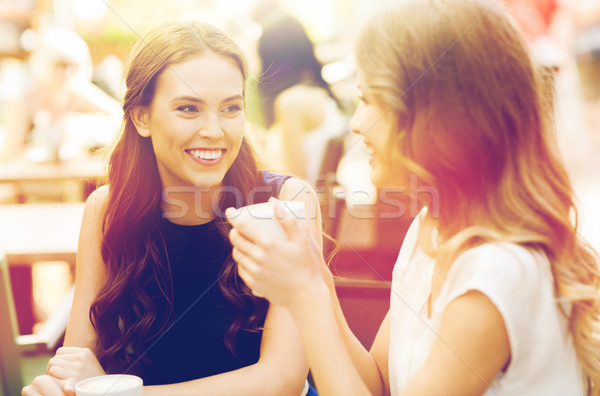 Stock photo: smiling young women with coffee cups at cafe