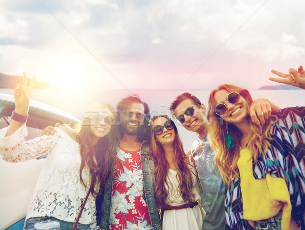 hippie friends at minivan car showing peace sign Stock photo © dolgachov