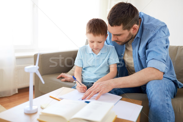father and son with toy wind turbine at home Stock photo © dolgachov