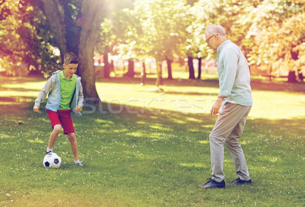 old man and boy playing football at summer park Stock photo © dolgachov