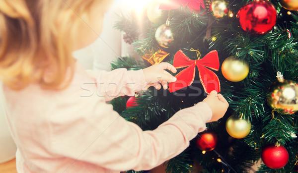close up of little girl decorating christmas tree Stock photo © dolgachov