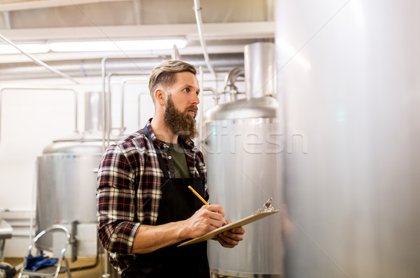 Stock photo: man with clipboard at craft brewery or beer plant