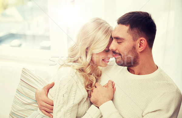 happy couple covered with plaid on sofa at home Stock photo © dolgachov