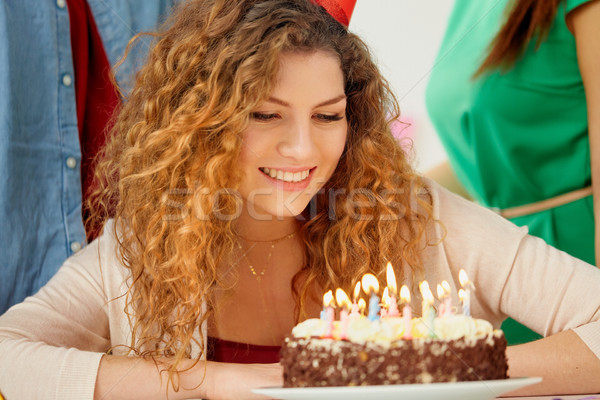 Stock photo: happy woman with candles on birthday cake at party
