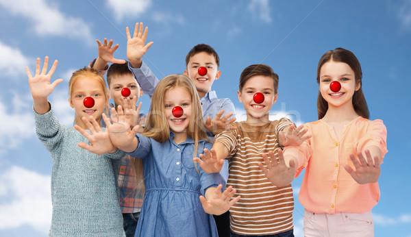 happy children waving hands at red nose day Stock photo © dolgachov