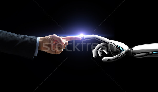 robot and human hand flash light over black Stock photo © dolgachov