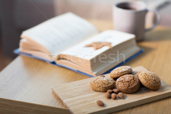 oat cookies, almonds and book on table at home Stock photo © dolgachov