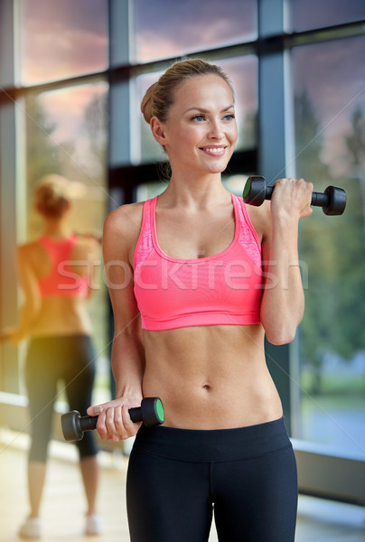 young sporty woman with dumbbells flexing biceps Stock photo © dolgachov