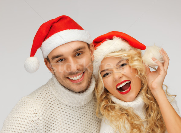 family couple in sweaters and santa's hats Stock photo © dolgachov