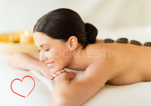 smiling woman in spa salon with hot stones Stock photo © dolgachov