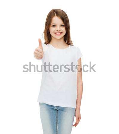 Uśmiechnięty dziewczynka biały tshirt projektu wskazując Zdjęcia stock © dolgachov