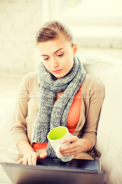 Stock photo: diseased woman in scarf using laptop at home
