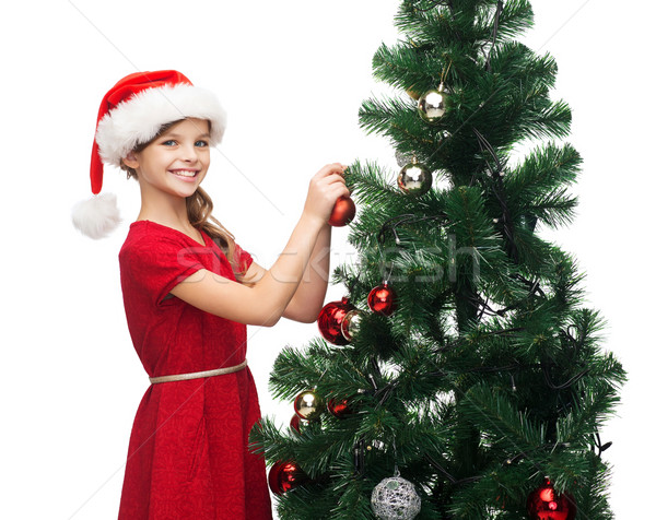 smiling girl in santa helper hat decorating a tree Stock photo © dolgachov