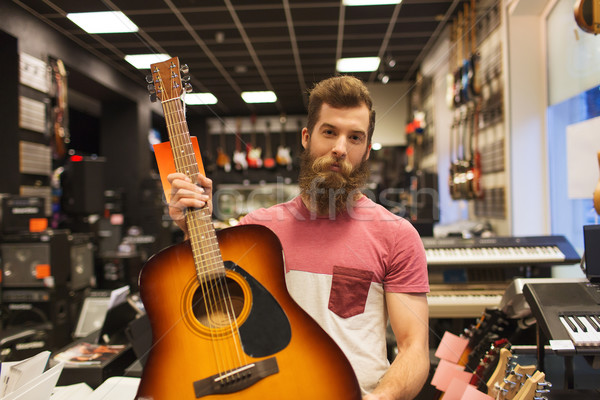 assistant or customer with guitar at music store Stock photo © dolgachov