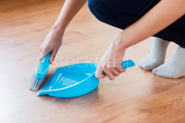 close up of woman with brush and dustpan sweeping Stock photo © dolgachov